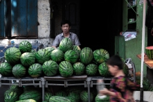 A watermelon merchant on a bustling Urumqi backstreet.