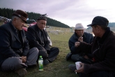 A group of Kazakh elders socialize and drink in the early evening.