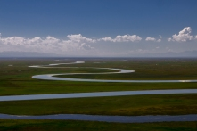 The magnificent river that snakes along a vast grassland.